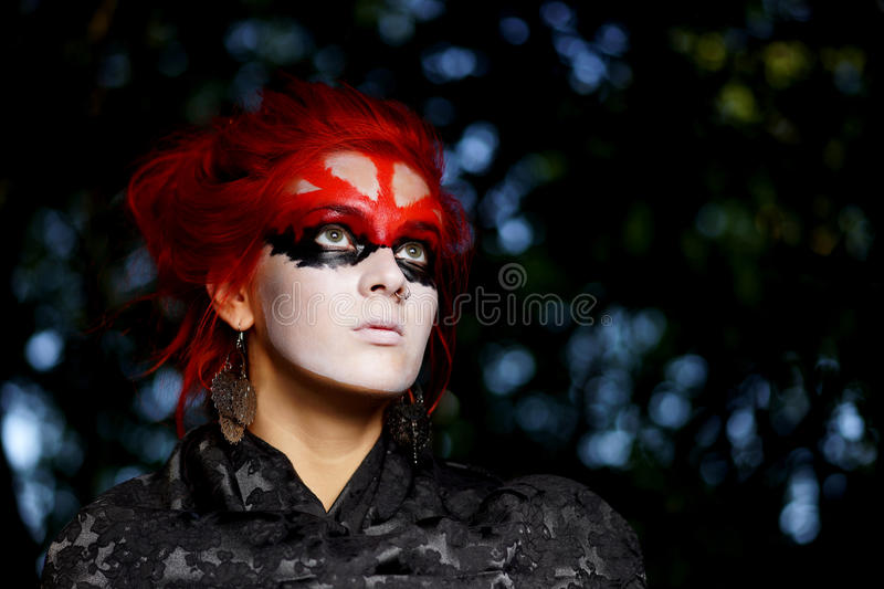 Woman with red hairs and black make-up mask. Beauty young caucasian woman with red hairs and black make-up mask stock photo