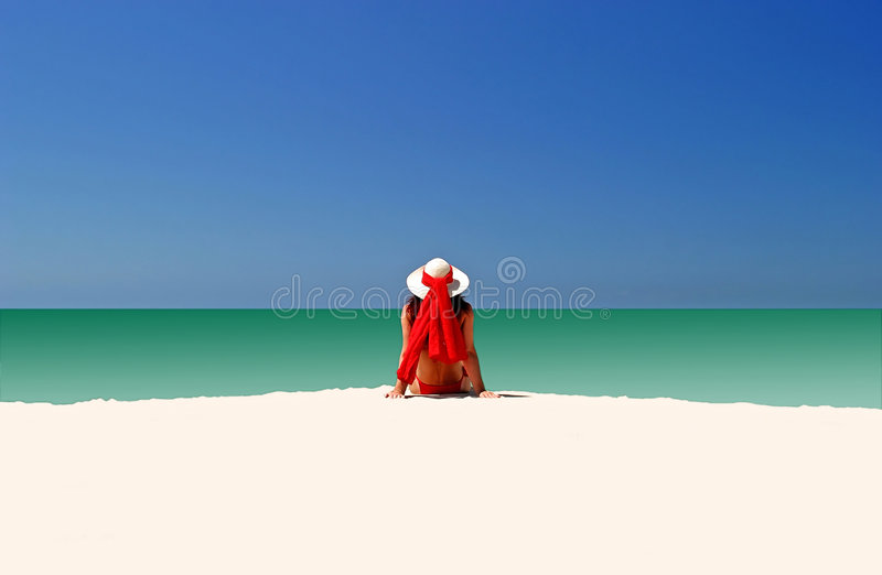 Woman in Red hat and bikini sitting all alone on empty beach stock photos