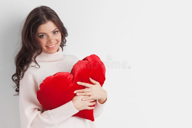 Woman with red heart shape pillow stock image
