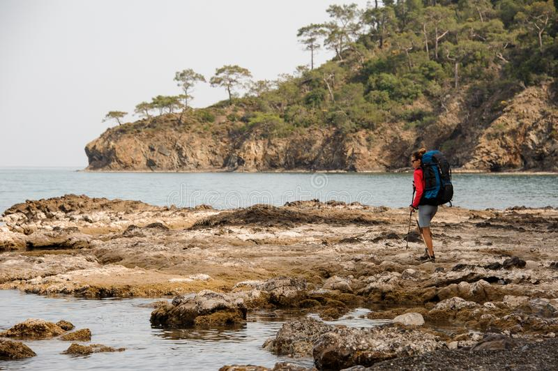 Woman with backpack hikes on sea coast royalty free stock images