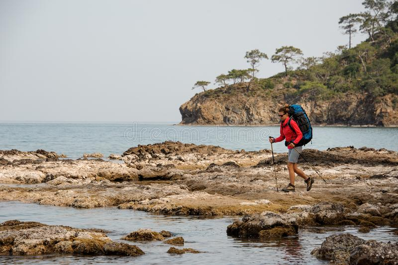 Woman with backpack hiking on a sea coast stock photo