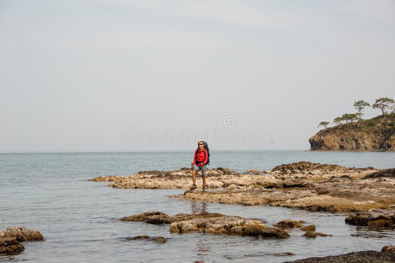 Woman with backpack travels on sea coast royalty free stock photos