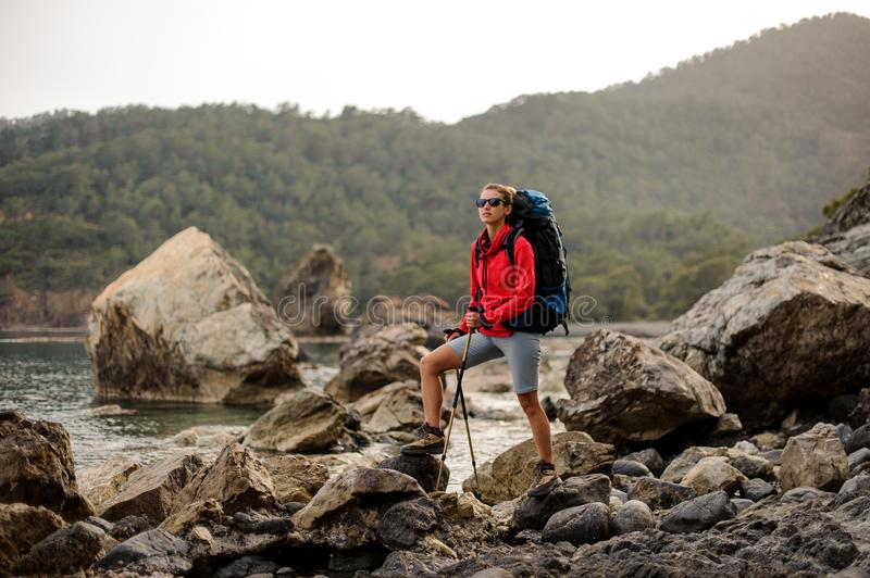 Woman with hiking equipment travelling through rocky coast stock photo