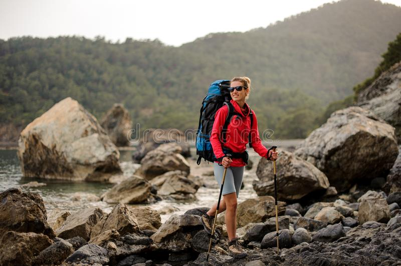 Woman with hiking equipment trekking through rocky coast royalty free stock image