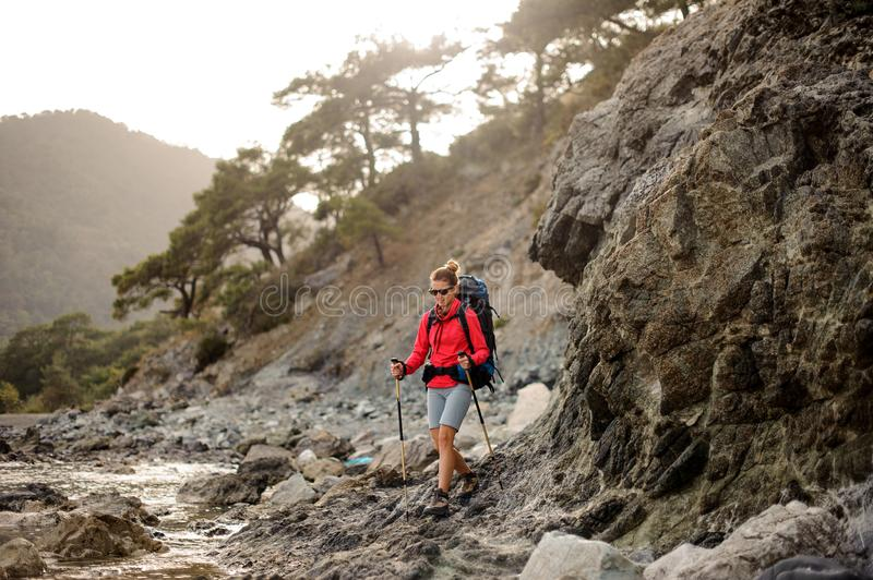 Woman with hiking equipment trekking through stoney coast royalty free stock photo