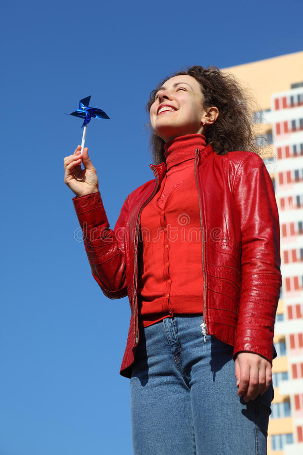 Woman in red jacket and jeans playing with spinner. Beautiful young woman in red jacket and blue jeans playing with blue spinner. in background yellow multi stock images