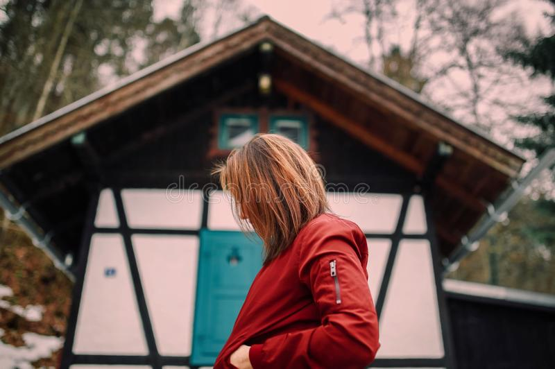 Woman in Red Jacket Standing Near Brown and White Wooden House royalty free stock photo