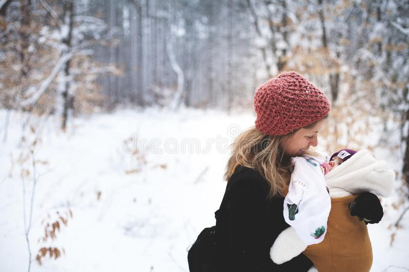 Woman in Red Knitted Cap and Black Top Holding Baby With Brown Carrier royalty free stock photo