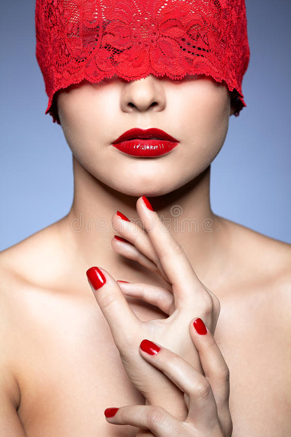 Woman with red lacy ribbon on eyes stock photo