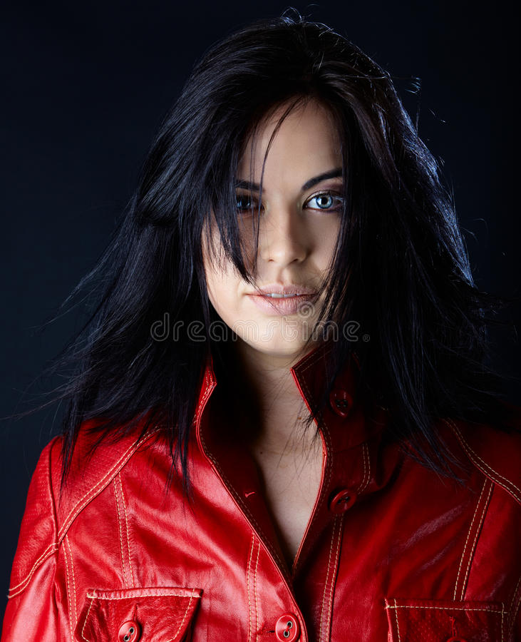 Woman in red leather jacket. Beautiful woman in red leather jacket and blowing hair on dark studio background stock images