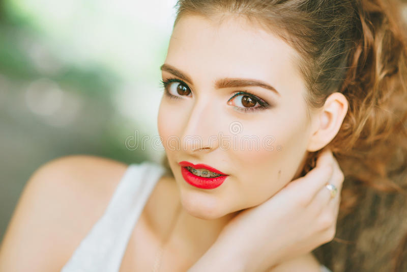 Woman with red lipstick and colored makeup, portrait in nature. Looking at the camera. stock photos