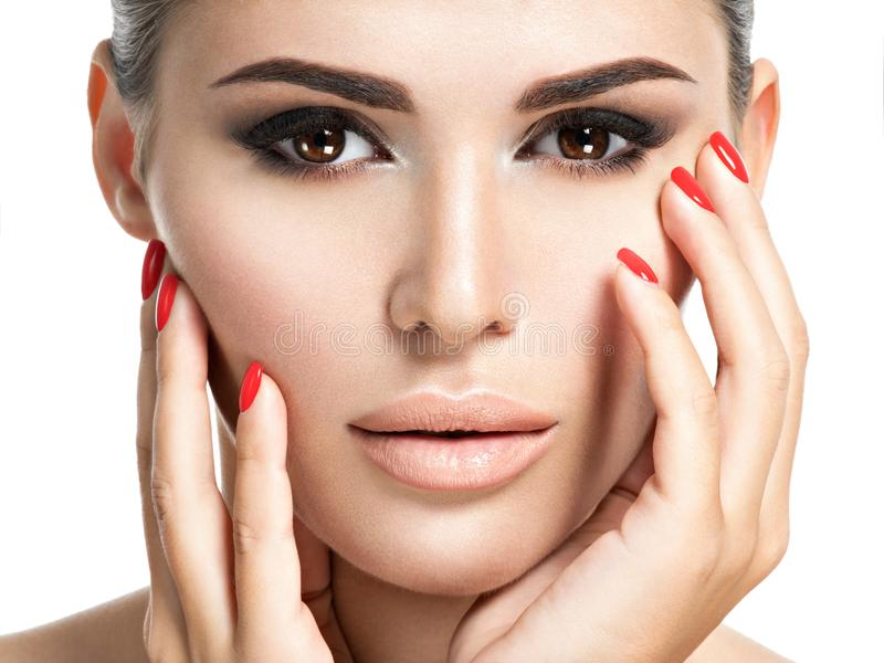 Woman with red nails and brown makeup. Portrait of young woman with red nails and brown makeup. Closeup portrait with a pretty female face royalty free stock photography