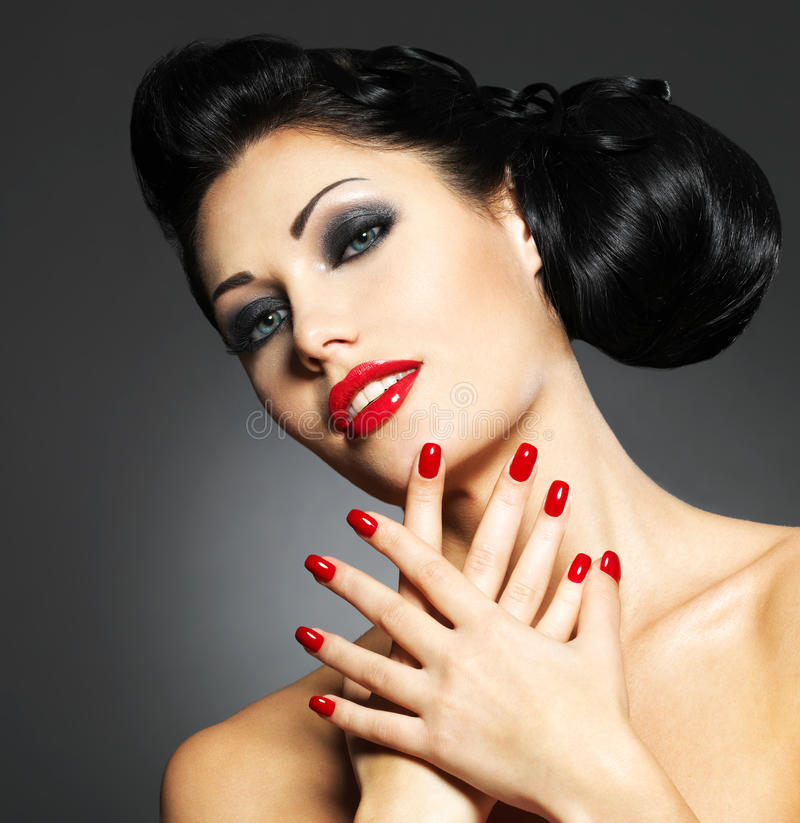 Woman with red nails and creative hairstyle. Beautiful fashion woman with red nails, creative hairstyle and makeup - Model posing in studio stock images