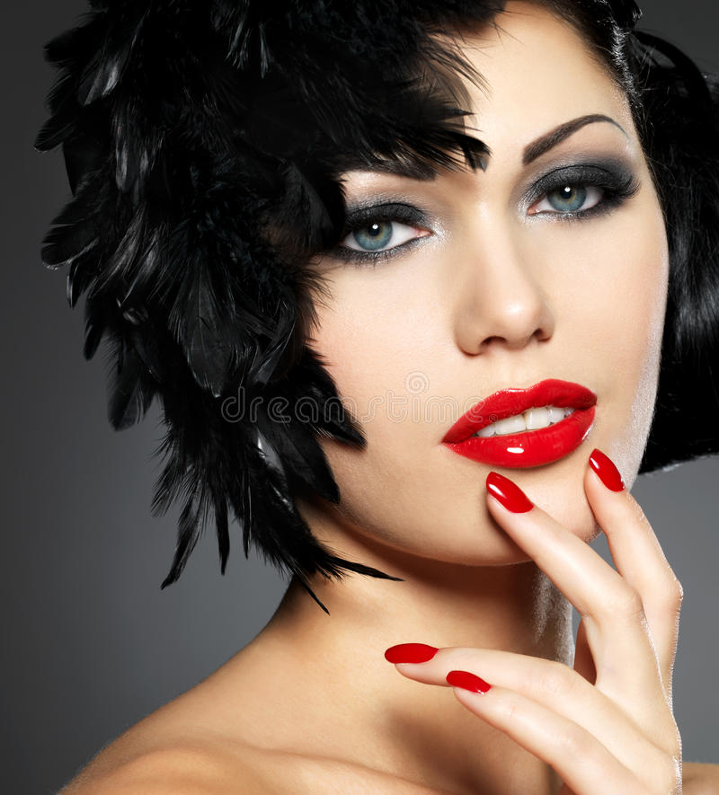Woman with red nails and creative hairstyle. Beautiful fashion woman with red nails, creative hairstyle and makeup - Model posing in studio royalty free stock photo