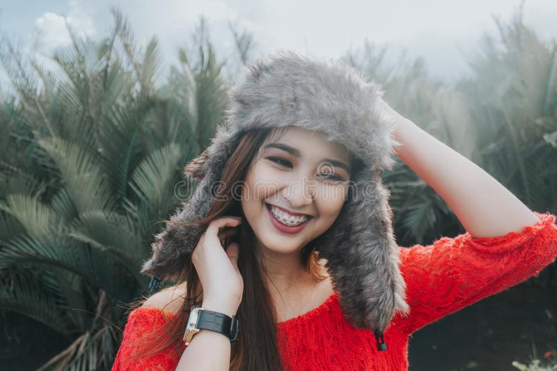 Woman In Red Off Shoulder Top Wearing Fur Beanie Smiling for Photo royalty free stock photography