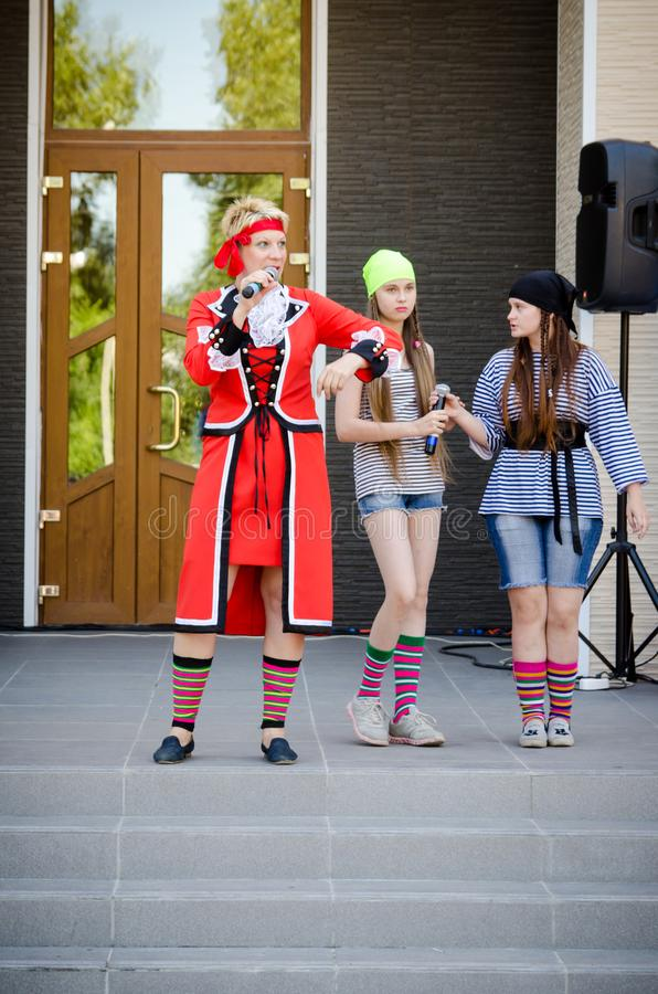 Woman in a red pirate costume leading a concert with a microphone in her hand stock photography