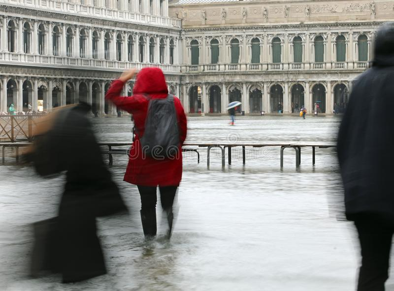 Woman with red rain coat in Saint Mark square in Venice Italy. Whitel raining during the flood stock photos