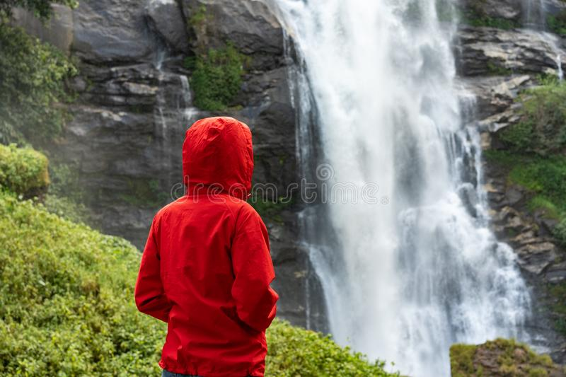 Woman hiker looking on waterfall outdoor. Tourism concept stock photography