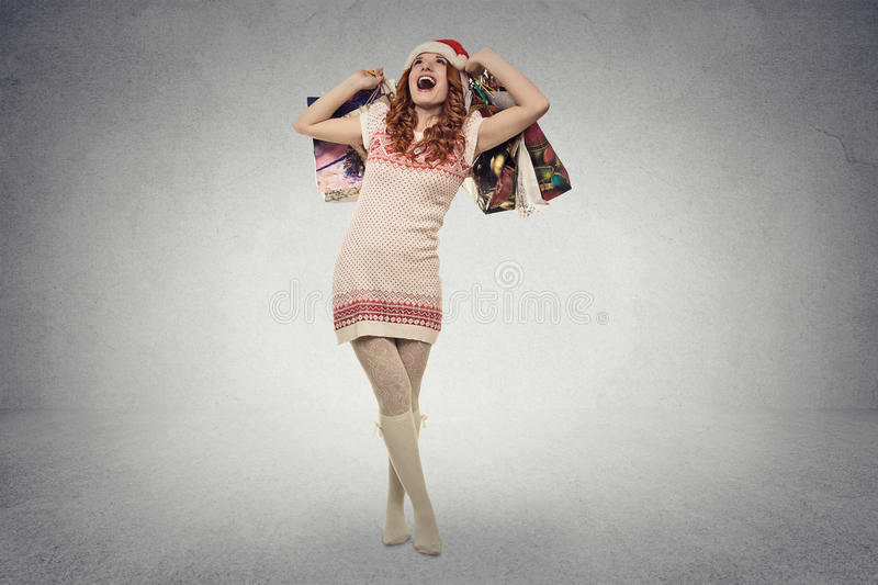 Woman in red santa claus hat with christmas gifts, shopping bags royalty free stock photo