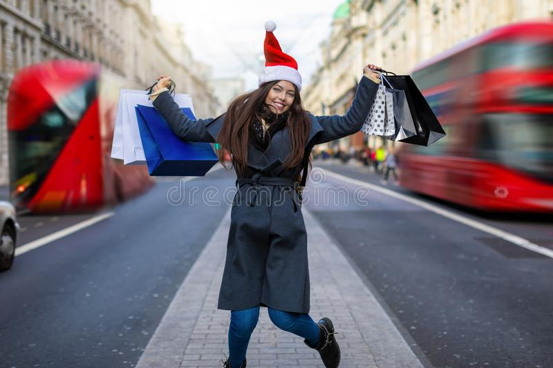 Woman with red Santa hat on the Regent Street in London, United Kingdom stock photo