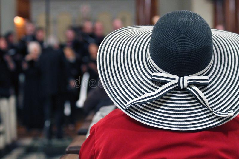 Woman in Red Shirt and Black and White Stripes Sunhat Surrounded by People royalty free stock image