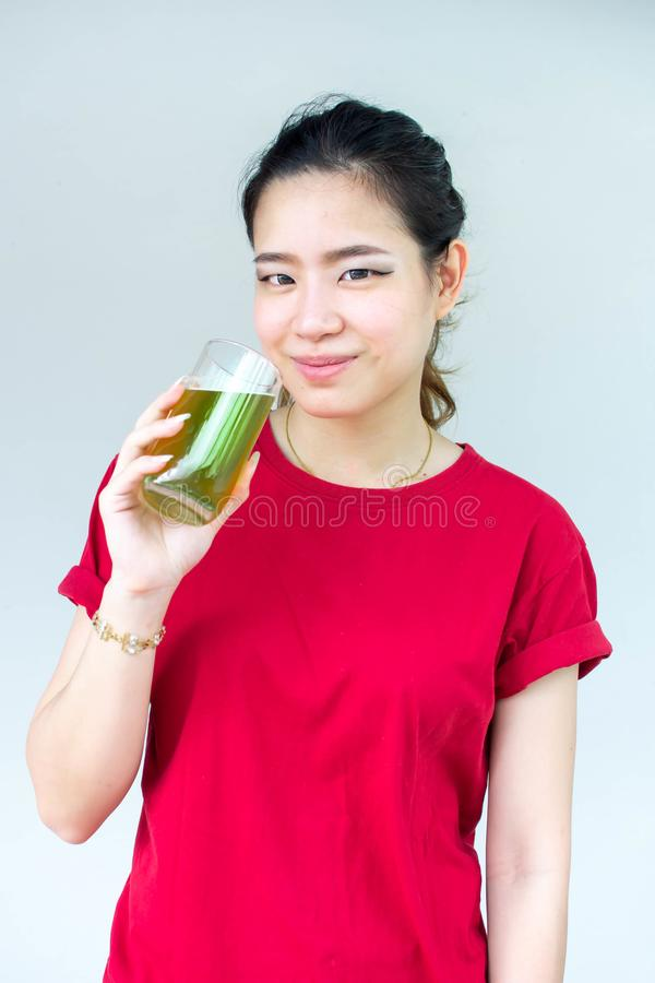 Woman in red shirt holding a glass of green tea royalty free stock images