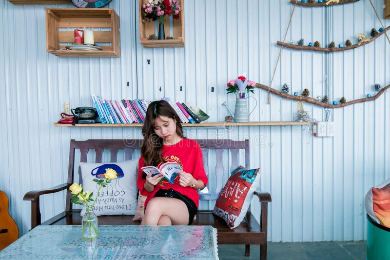 Woman in Red Shirt Reading Book While Sitting on Bench royalty free stock photo
