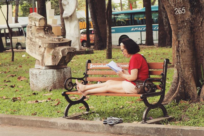 Woman In Red Shirt Sitting On Bench royalty free stock images