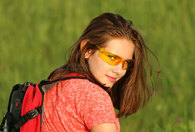Woman in Red Shirt Wearing Backpack Surrounded by Green Grass Field royalty free stock images