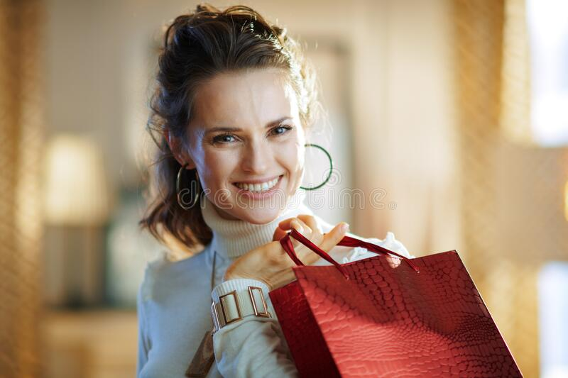 Woman with red shopping bag in modern house in sunny winter day royalty free stock images