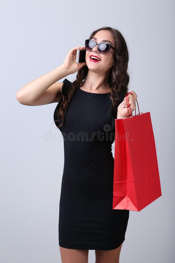 Woman with red shopping bag and smartphone royalty free stock images