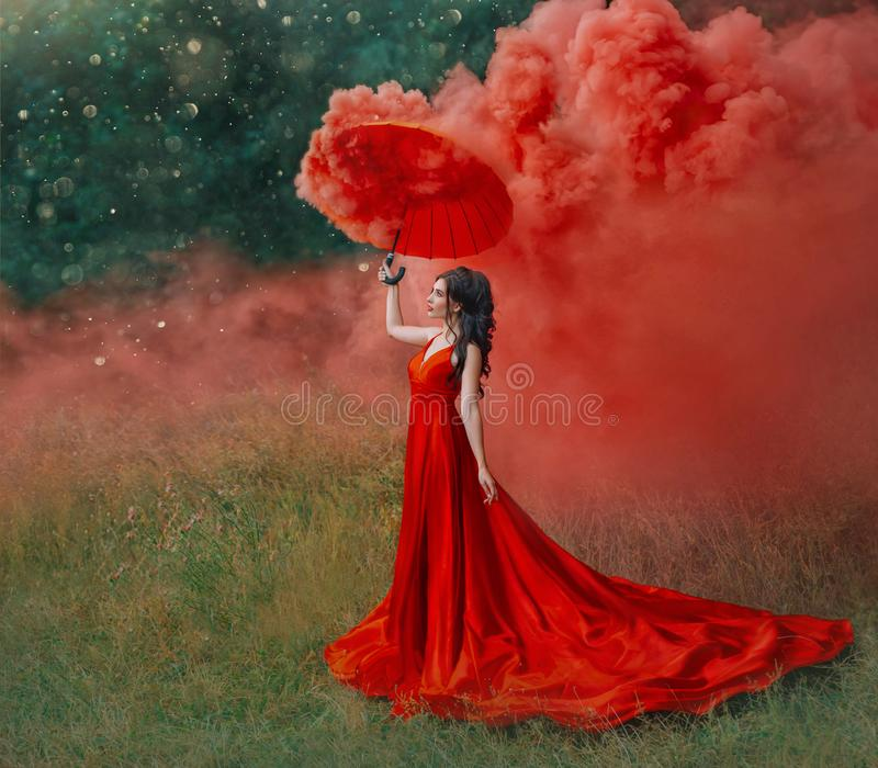 Woman in red silk long dress train with umbrella. Art design photography. royalty free stock photos