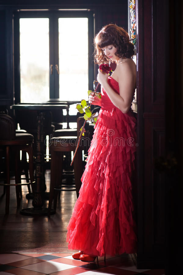 Woman In Red Smelling Rose Royalty Free Stock Photo