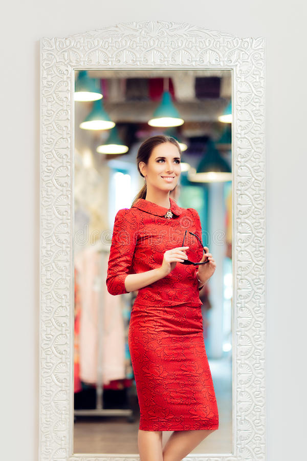 Woman in Red Suit in Fashion Store. Self-confident Stylish diva standing in fitting room stock photo