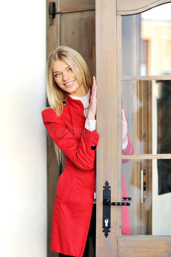 Woman in red suit looks out the door royalty free stock photography