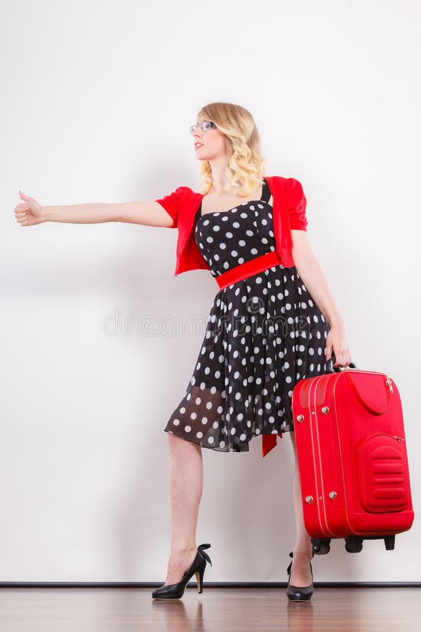Woman with red suitcase hitchhiking. Traveling vacation ew life concept. Elegant lovely woman wearing polka dot black dress with red suitcase ready for trip stock photos