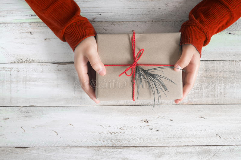 A woman in a red sweater holding a Christmas gift with a red ribbon on a wooden table. royalty free stock photography