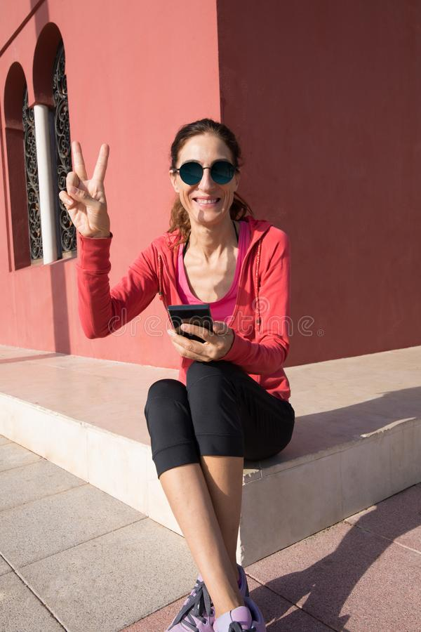 Happy woman sitting with phone and victory sign with fingers. Woman with red sweater and mobile phone sitting in the corner of ocher building with symmetry walls royalty free stock photo