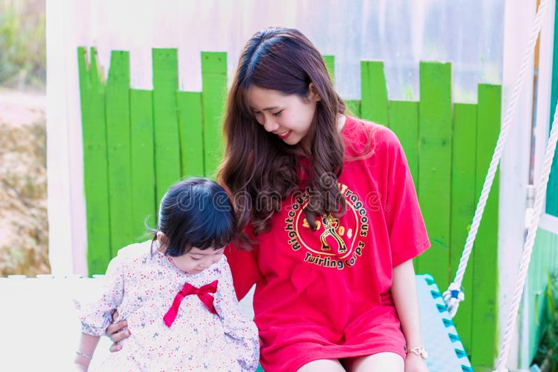 Woman in Red T-shirt Sitting Beside Girl royalty free stock photography