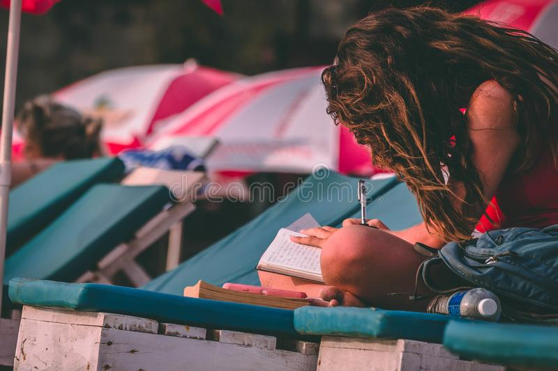 Woman With Red Top Holding Pen and Notebook royalty free stock photos