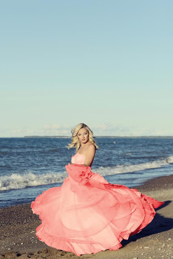 Woman in red tulle dress dancing at the beach royalty free stock image