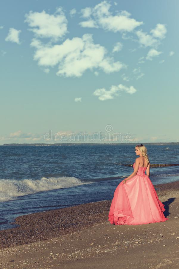 Woman in red tulle evening dress by ocean stock photo