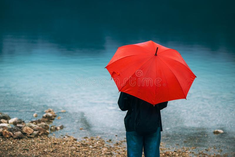 Woman with red umbrella contemplates on rain. In front of a lake. Sad and lonely female person looking into distance stock photos