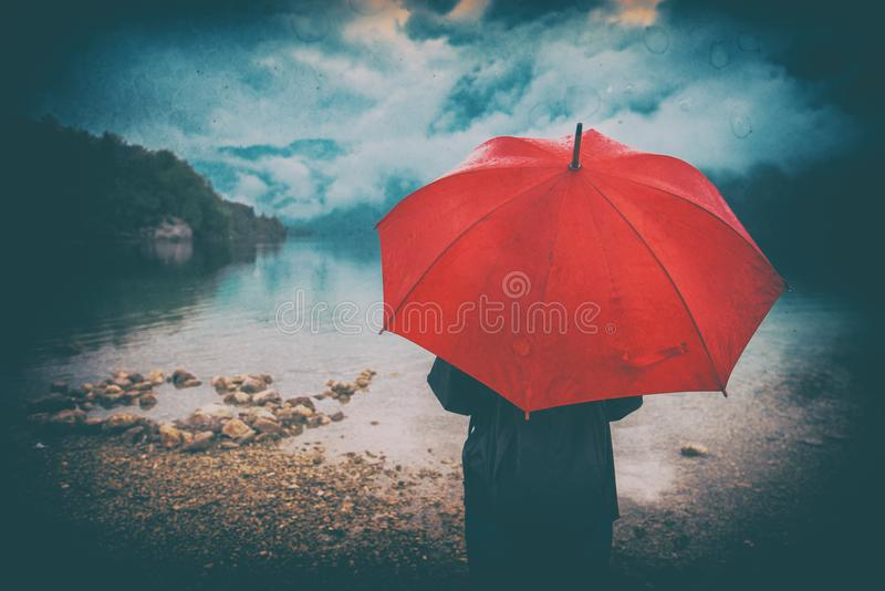 Woman with red umbrella contemplates on rain royalty free stock image