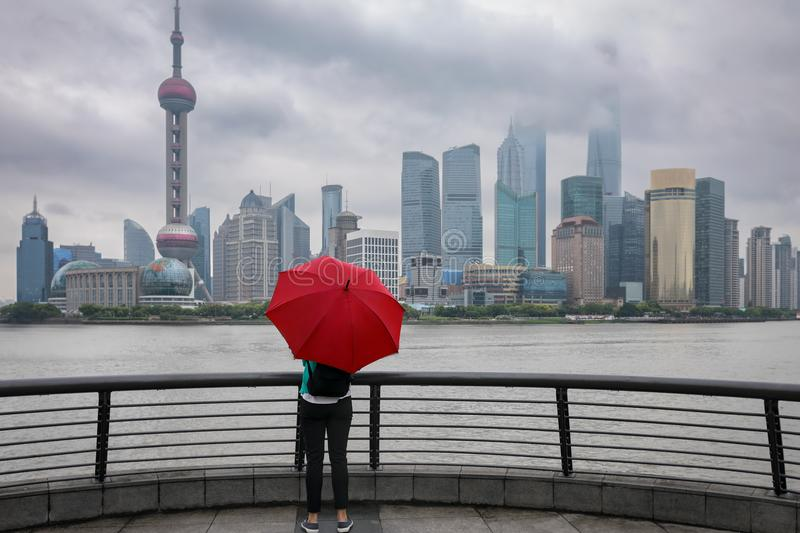 Woman with red umbrella enjoys the view to the skyline of Shanghai, China stock image