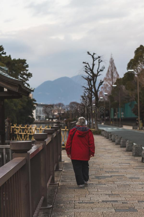 Woman in red walking to the temple on a cold day stock image