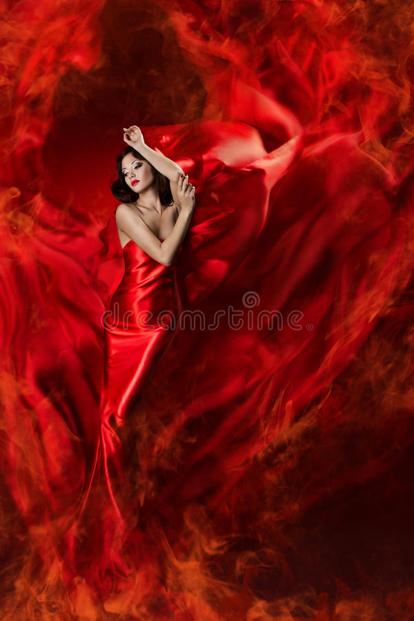 Woman in red waving dress as fire flame. Woman in red waving silk dress as a fire flame. Artistic Beauty Model girl posing in flying long gown