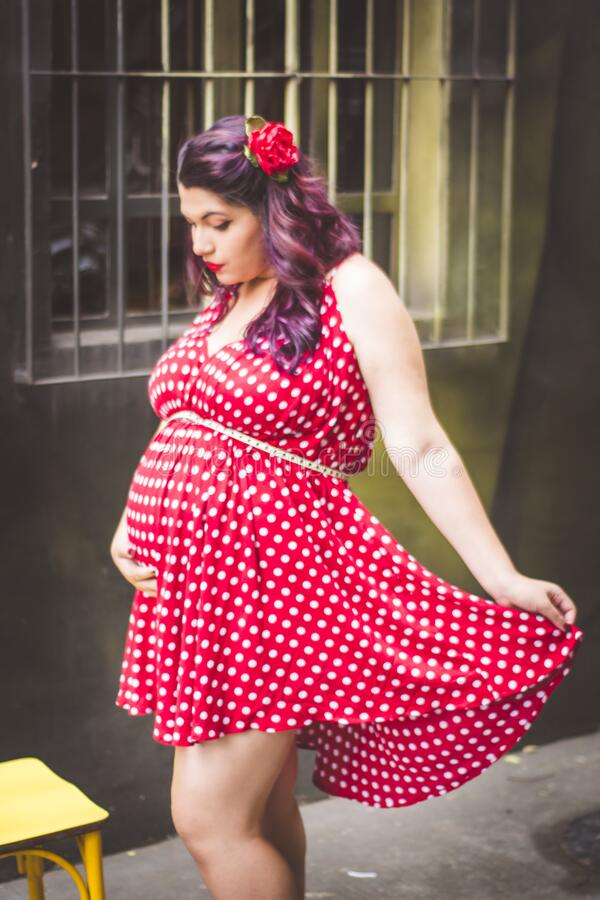 Woman in Red and White Polka Dots Mini Dress Holding Her Stomach royalty free stock images