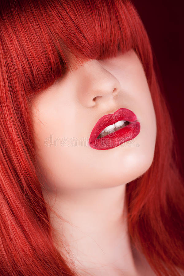 Woman with red wig over the eye on dark red background stock images