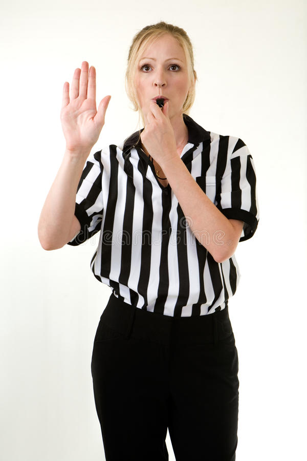 Woman referee. Attractive blonde woman wearing black and white striped referee uniform blowing on a whistle making a hand signal stock images